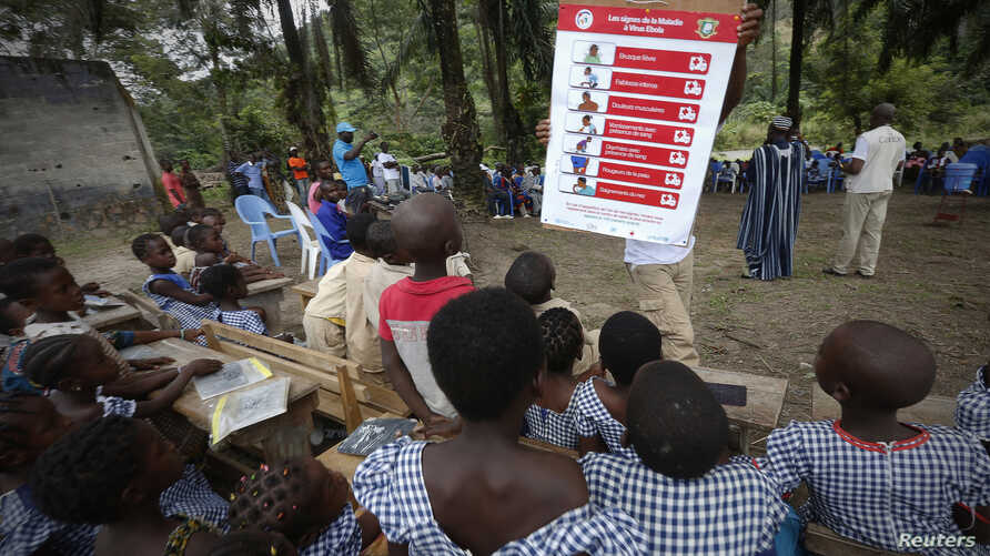 A man shows students a poster on the symptoms of Ebola during a United Nations Children's Fund (UNICEF) Ebola awareness drive in Gueupleu, Man, western Ivory Coast, Nov. 3, 2014.