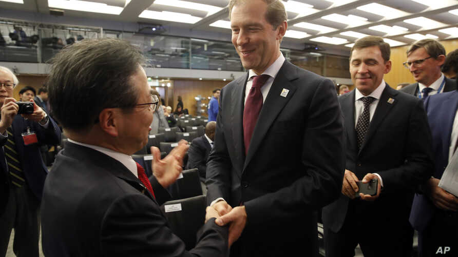 Russian Minister of Industry and Trade Denis Manturov (R) speaks with Japan's Economy, Trade and Industry Minister Hiroshige Seko at the 164th General Assembly of the Bureau International des Expositions (BIE) in Paris, Nov. 23, 2018.