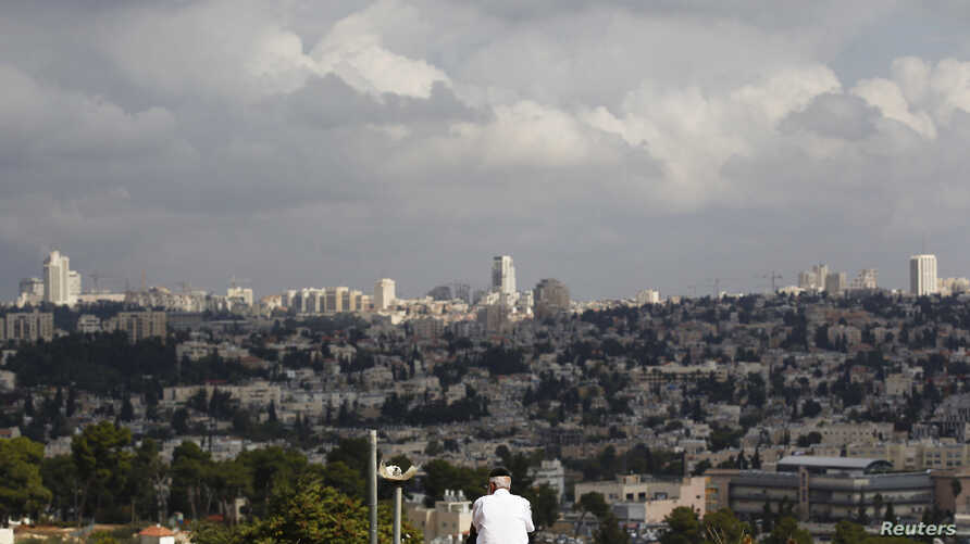 A view of Jerusalem is seen in the background as a man sits in Giv'at HaMatos, a neighbourhood on the southern fringes of Jerusalem's city limits where according to anti-settlement watchdog Peace Now,  Israel decided to move forward on a settler hous