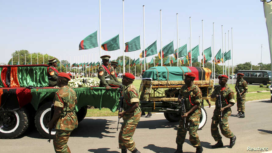 Flags fly at half mast as the funeral cortege for the late Zambian President Michael Sata arrives for a memorial service in the capital Lusaka, Zambia, Nov. 10, 2014.