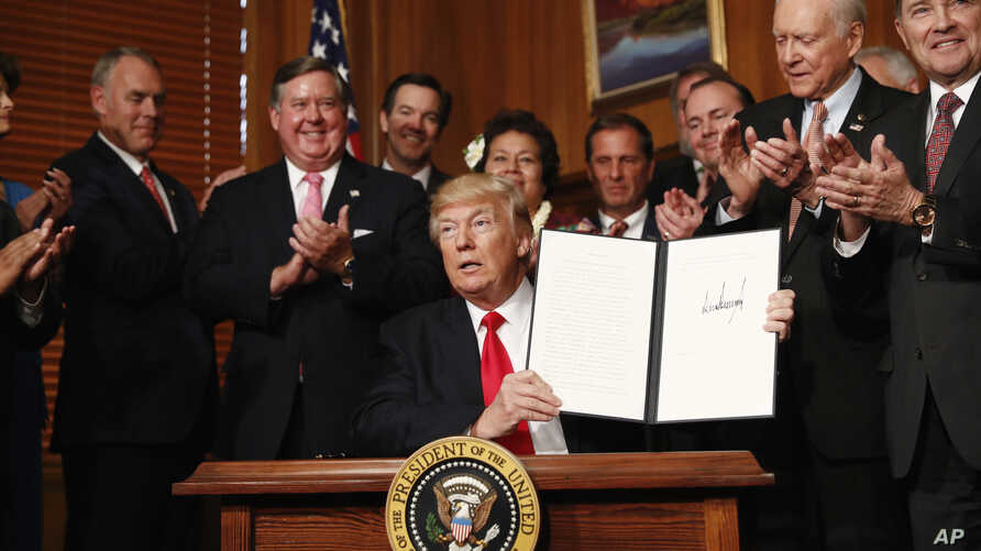 U.S. President Donald Trump holds up a signed Antiquities Executive Order during a ceremony at the Interior Department in Washington, April, 26, 2017.
