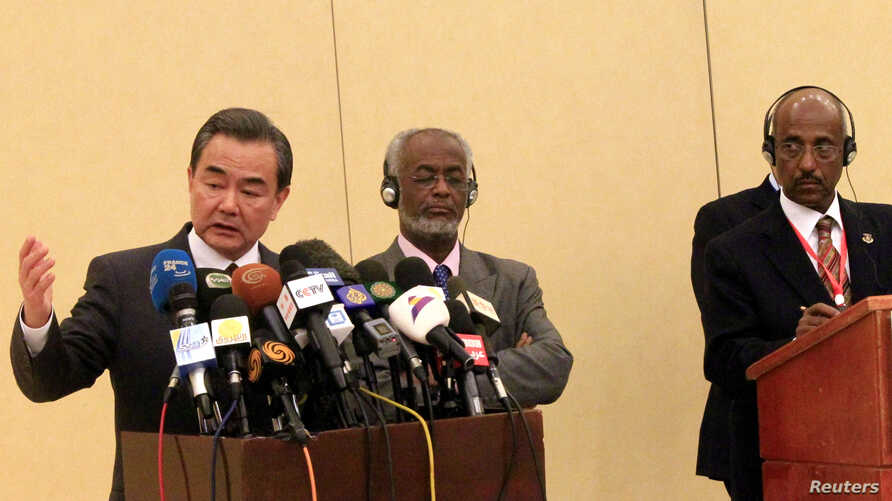 Chinese Foreign Minister Wang Yi (L) speaks during joint news conference with Tedros Adhanom, former Ethiopia's Foreign Minister, and Chair of the IGAD Council of Ministers and Sudan's Foreign Minister Ali Karti (C) after a special consultation in su