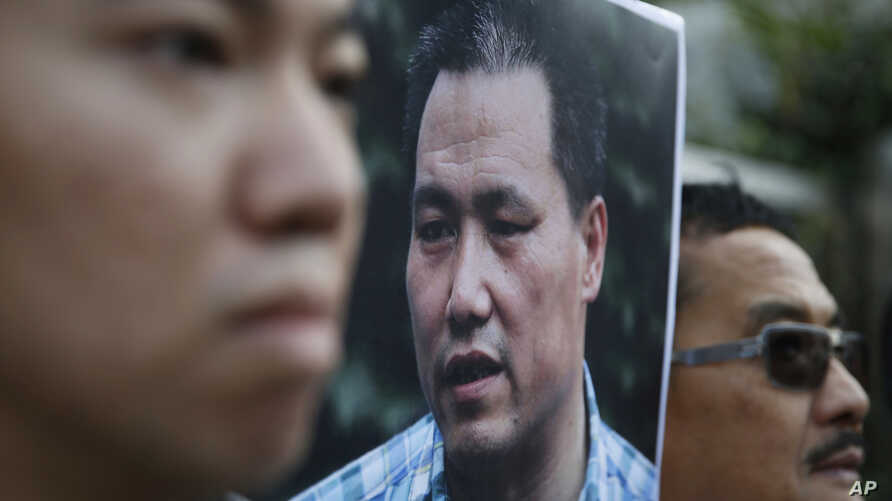 FILE - Anti-Beijing protesters, with a picture of human rights lawyer Pu Zhiqiang, protest outside the Chinese liaison office to demand Pu's release, in Hong Kong, Tuesday, Dec. 15, 2015.