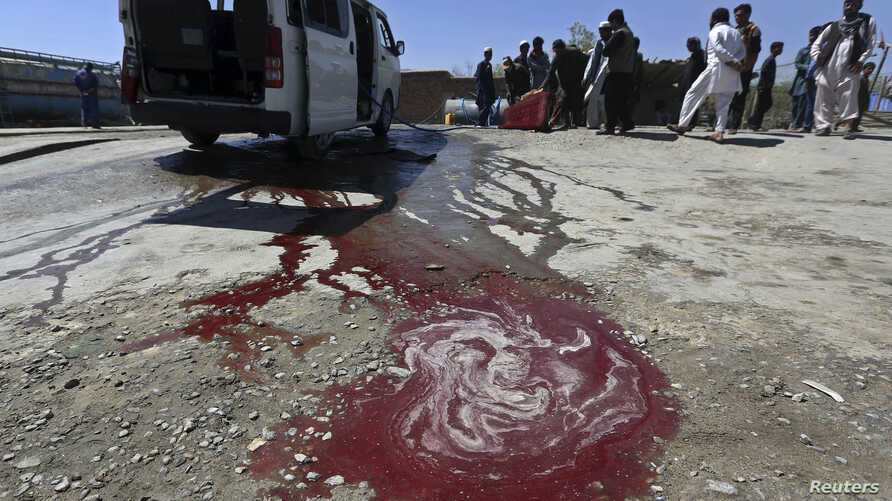 Afghan residents watch as a man washes a damaged minivan after was hit by a remote-controlled bomb in Kabul, July 15, 2014.