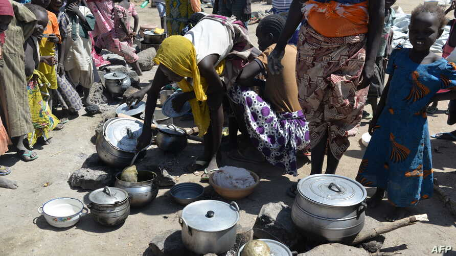 Wopmen prepare food on November 13, 2014 in a camp for Nigerian refugees in Minawao, in the extreme north-west of Cameroon. Almost 17,000 Nigerians in this camp have fled their country , terrified of raids by the Islamists of Boko Haram.. AFP PHOTO: