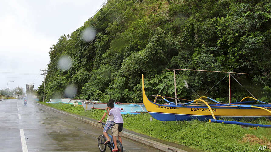 Boys pedal their way past boats placed on a safer area in Legazpi city, central Philippines as Typhoon Melor slammed into the eastern Philippines, Monday, Dec. 14, 2015.