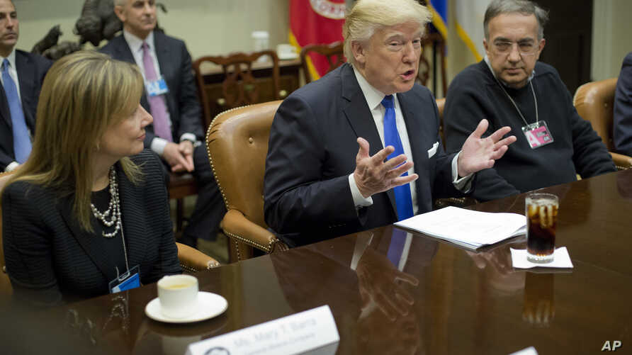 President Donald Trump, flanked by GM CEO Mary Barra and Fiat Chrysler Automobiles CEO Sergio Marchionne, gestures while speaking at the start of a meeting with automobile leaders in the Roosevelt Room of the White House in Washington, Jan. 24, 2017.