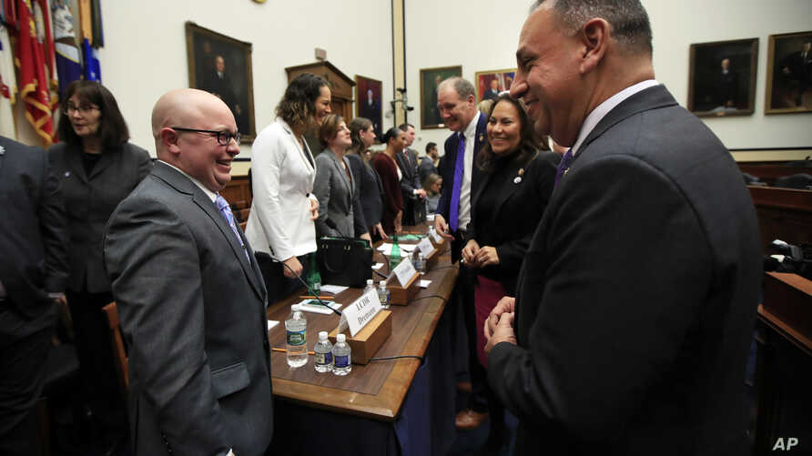 Rep. Gil Cisneros, D-Calif., right, talks to Navy Lt. Cmdr. Blake Dremann, left, and other transgender military members at the conclusion of a House Armed Services subcommittee hearing in Washington, Feb. 27, 2019.