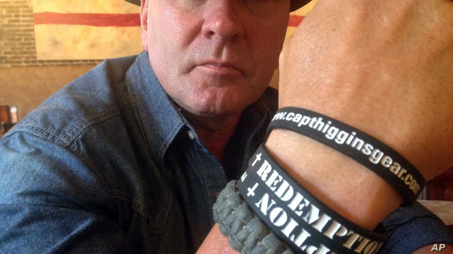 """FILE - In this June 2, 2016, photo, Clay Higgins, then a candidate for Congress, poses for a photograph in Lafayette, La. His wristband is printed with the word """"redemption."""" The Republican dubbed the """"Cajun John Wayne"""" set his sights on and won a co"""