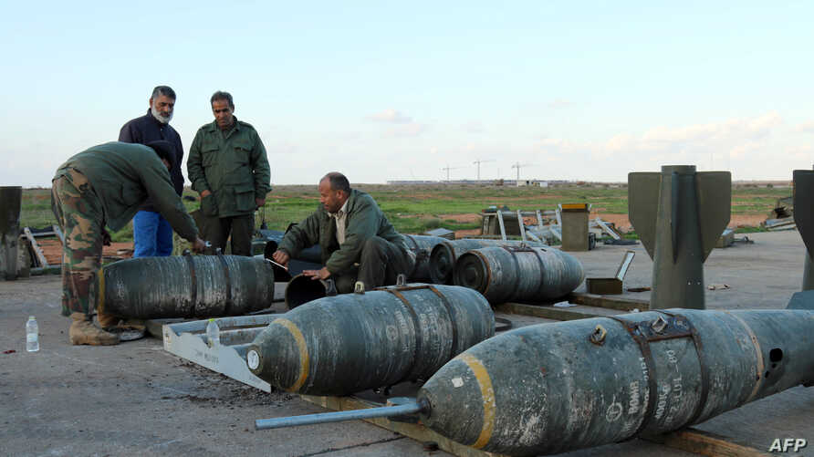 Libyan soldiers loyal to Libya's internationally recognized government work next to bombs at the Benina air base on Dec. 10, 2015, south of Libya's eastern coastal city of Benghazi.