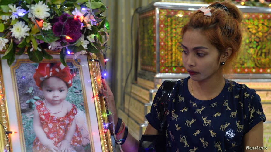 Jiranuch Triratana, mother of an 11-month-old girl who was killed by her father who broadcast the slaying on Facebook, stands next to a picture of her daughter, Natalie, at a temple in Phuket, Thailand, April 25, 2017.