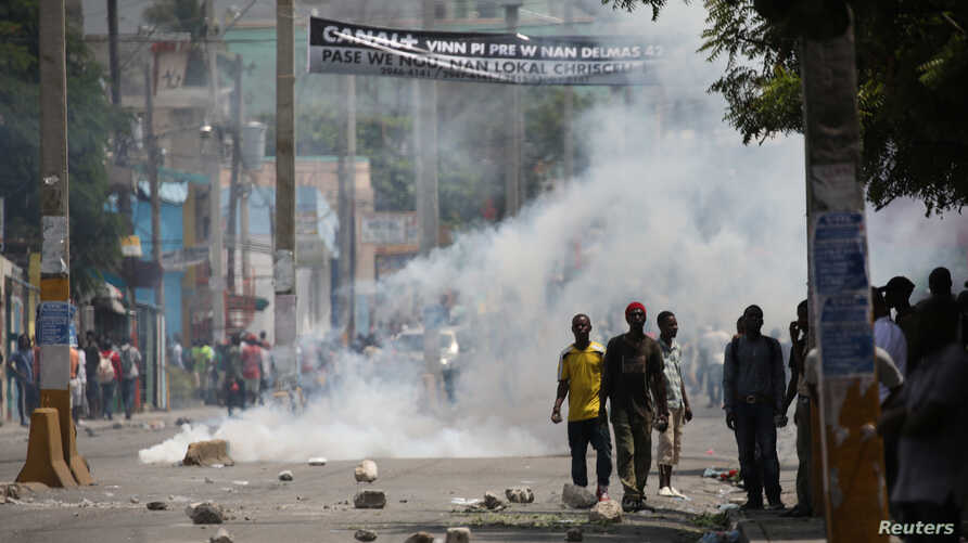 Protesters stand next to tear gas rising up during clashes at a demonstration against the government in Port-au-Prince, Haiti, Sept. 12, 2017.
