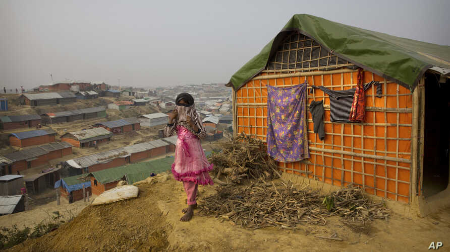 A Rohingya Muslim girl wears a sweater standing outside her tent at Balukhali refugee camp 50 kilometres (32 miles) from Cox's Bazar, Bangladesh, Jan. 14, 2018.