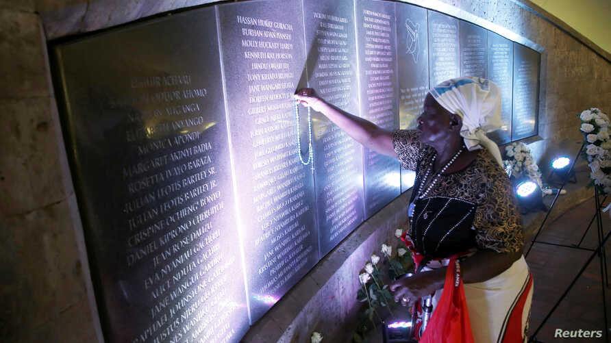 Margaret Achieng Jow, who's daughter Doreen was killed in the 1998 U.S. Embassy in Nairobi bombing, holds a cross on a wall displaying the names of people killed during the attack at a ceremony marking the 20th anniversary of the bombing at the Augus