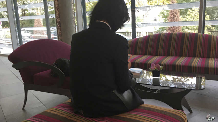 Grace Meng, the wife of missing Interpol President Meng Hongwei, who does not want her face shown, consults her mobile phone in the lobby of a hotel in Lyon, central France, where the police agency is based, Oct. 7, 2018.