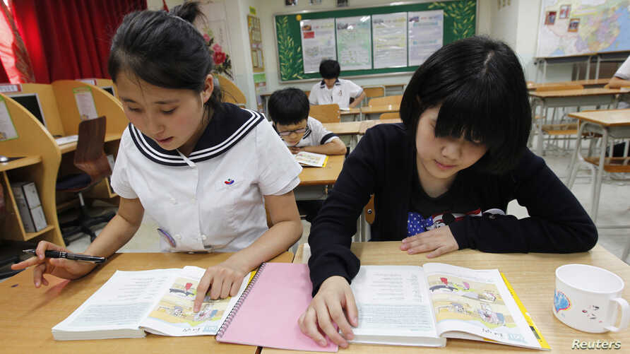 FILE - Lim Myeong-hee (L), 16, and her friend, middle school students who defected from North Korea, memorize English words as they look at English textbooks during supplementary lessons at the Hangyeore Middle and High School in Anseong, about 80 km
