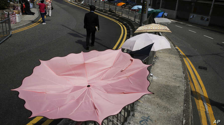 A man walks past an umbrella installation in the occupied area outside government headquarters in Hong Kong's Admiralty, Oct. 28, 2014.