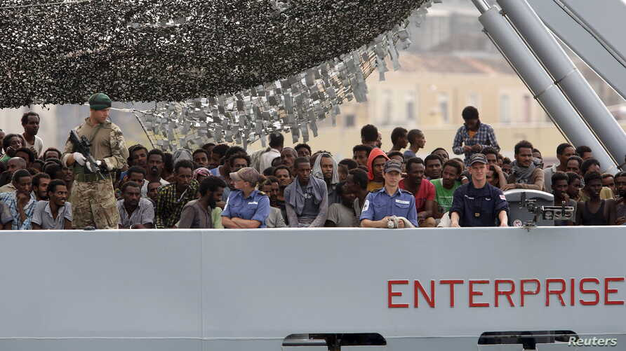 Migrants arrive on the British vessel HMS Enterprise before disembarking in the Sicilian harbor of Catania, Italy, Oct. 6, 2015. The Italian coastguard said on Tuesday some 1830 migrants were rescued from the Mediterranean sea in a twenty-four hour p