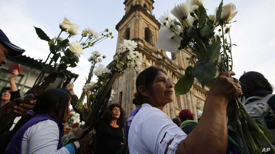 A woman holds flowers as she attends a peace march in Bogota, Colombia, Oct. 12, 2016.