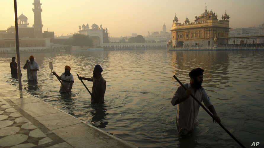 FILE- In this Nov. 17, 2013, file photo, Indian Sikh devotees clean the tank early in the morning at the Golden Temple, on the birth anniversary of Guru Nanak, the first Sikh Guru in Amritsar, India.