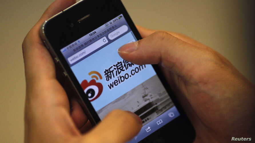 FILE - A man holds an iPhone as he visits Sina's Weibo (China's version of Twitter) microblogging site in Shanghai.
