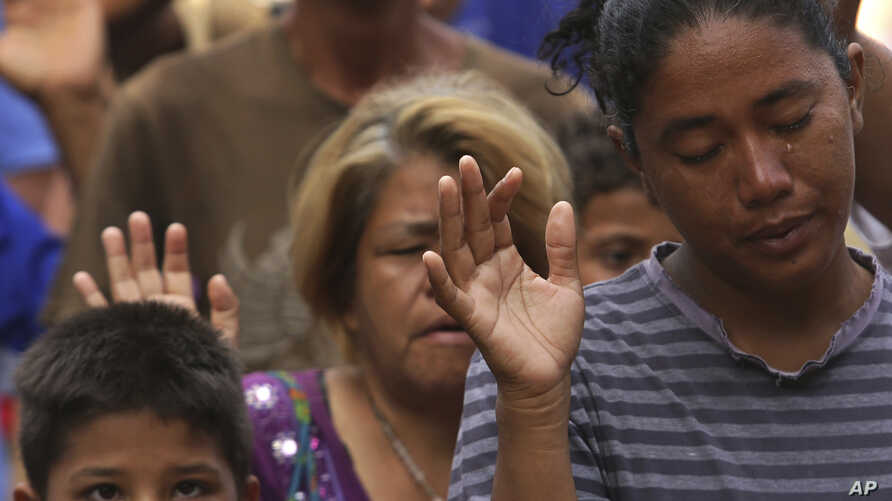 In this March 11, 2018 photo, a tear runs down the cheek of Venezuelan woman praying during religious service in Simon Bolivar Square where many are living in tents in Boa Vista, Roraima state, Brazil.