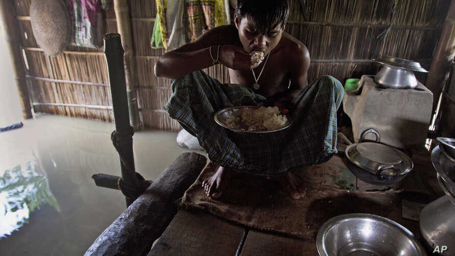 FILE - A boy eats rice inside his house partially submerged in flood waters at Gagolmari village 85 kilometers (53 miles) east of Gauhati, India, Sept. 2, 2015.
