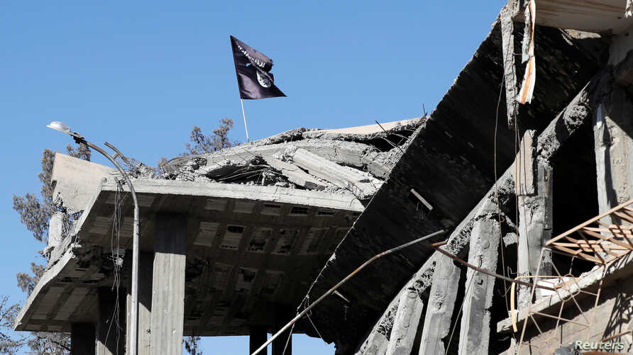 FILE - A flag of Islamic State militants is pictured above a destroyed house in Raqqa, Syria, Oct. 18, 2017.