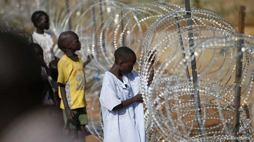 Internally displaced boys stand next to barbed wire inside a United Nation Mission in South Sudan (UNMISS) compound in Juba, Dec. 19, 2013.