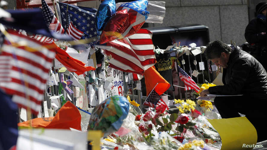FILE - A man kneels before a makeshift memorial for the victims of the Boston Marathon bombings on Boylston Street in Boston, Massachusetts April 22, 2013.