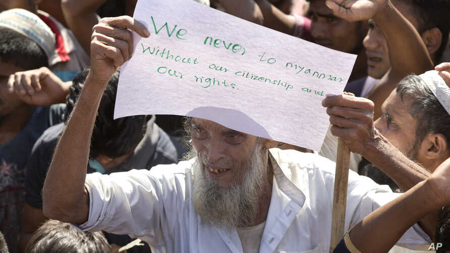 An elderly Rohingya refugee holds a placard during a protest against the repatriation process at Unchiprang refugee camp near Cox's Bazar, in Bangladesh, Nov. 15, 2018. The head of Bangladesh's refugee commission said plans to begin a voluntary repat