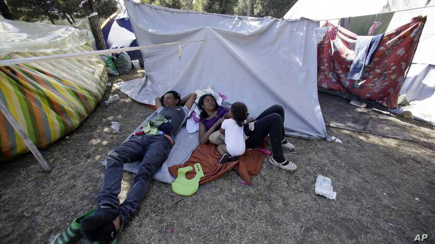 A Venezuelan refugee family rests outside a makeshift camp before going out to find any kind of work in Quito, Ecuador, Aug. 9, 2018.