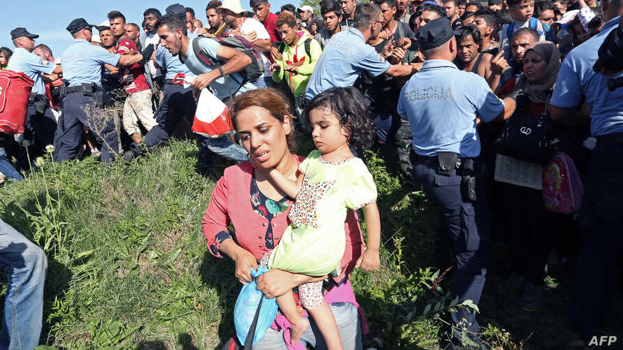 People break a police cordon as the rush to waiting buses at the train station in the city of Tovarnik, close to the Croatian-Serbian border, on Sept. 17, 2015.