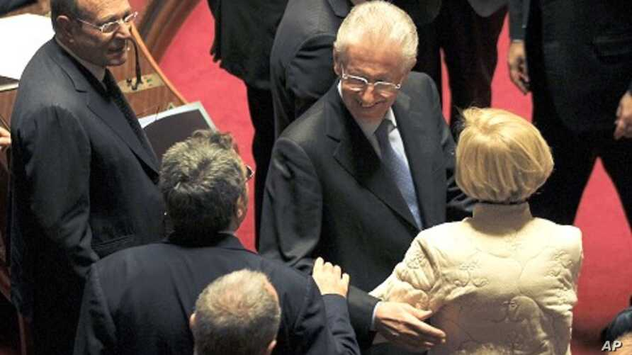 Former European Commissioner Mario Monti (2nd R) is greeted by senators as he arrives at the Senate in Rome November 11, 2011.