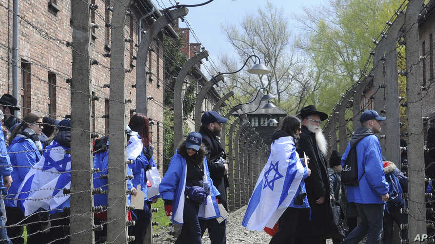 Participants of the yearly March of the Living walk through a barbed wire fence in the former German Nazi Death Camp Auschwitz-Birkenau, in Oswiecim, Poland, April 24, 2017.