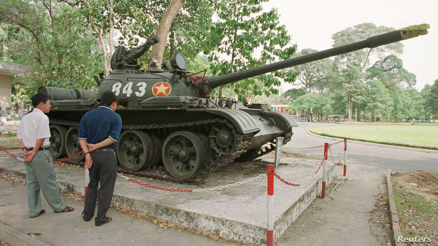 FILE - Tourists in Ho Chi Minh City look at Soviet-made tank number 843, made famous and preserved in situ since crashing through the gates of the former South Vietnamese presidential palace at the end of the Vietnam War in April 1975, Feb. 24, 2001.