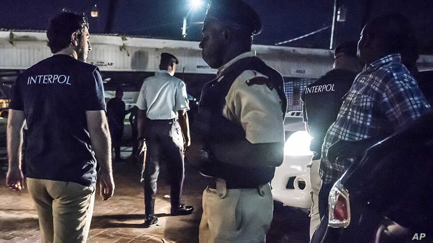 This photo made available by Interpol Monday April 30, 2018 shows Interpol officers during a raid in night clubs in Georgetown, Guyana, on April 7, 2018.
