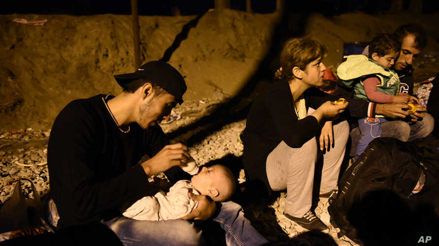 Syrian refugee Abed Hadi,19, feeds his nephew as he sits with other migrants beside railway tracks, waiting to cross the border from Idomeni, in northern Greece, to southern Macedonia, Sept. 1, 2015.