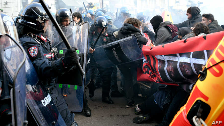 Police clash with demonstrators during an anti-fascist and anti-racist march to protest against a Northern League far-right party general election campaign rally in Milan, Italy, Feb. 24, 2018.