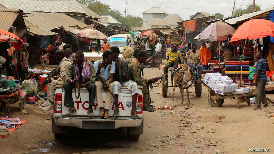 Somali soldiers patrol a street market following a suicide car bomb and gun attack on Tuesday that killed 11 people in Afgoye, Somalia, Oct. 19, 2016.