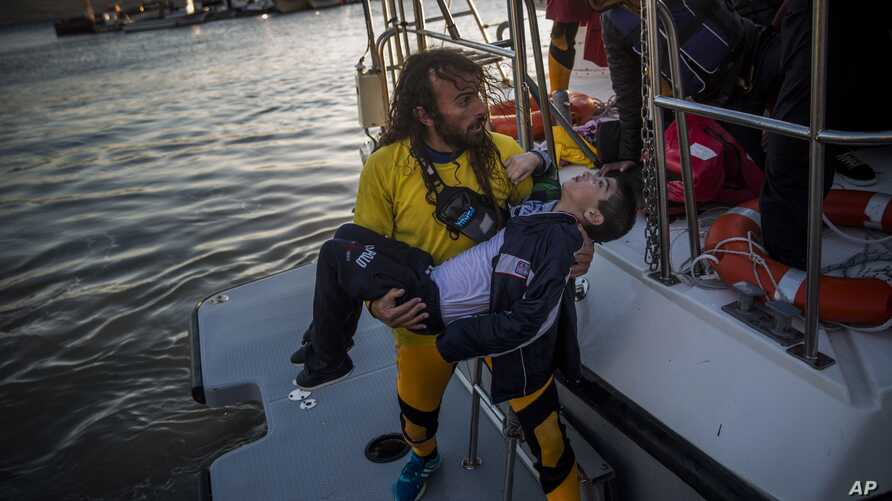 A volunteer carries a young boy after a boat with refugees and migrants sank while crossing the Aegean Sea from Turkey to the Greek island of Lesbos, Oct. 28, 2015.