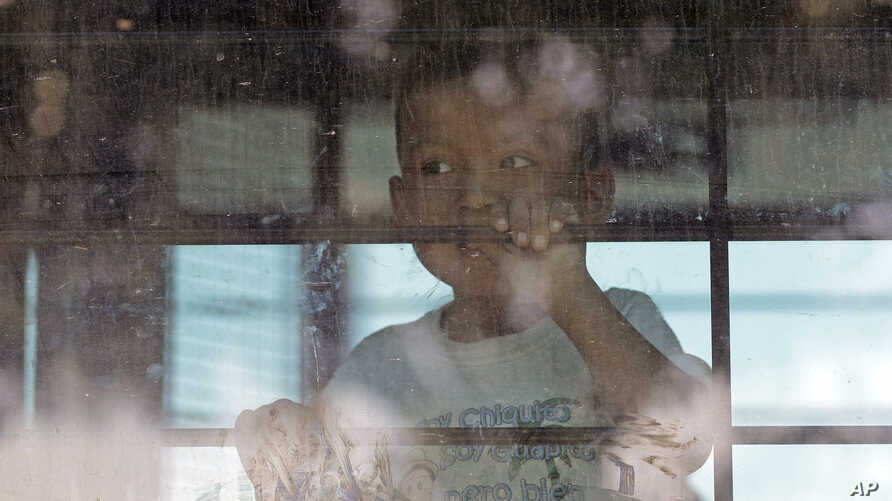 FILE - An immigrant child looks out from a U.S. Border Patrol bus leaving the U.S. Border Patrol Central Processing Center in McAllen, Texas, June 23, 2018.