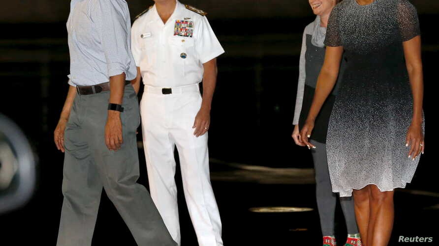 U.S. President Barack Obama, left, and first lady Michelle Obama, right, are greeted by U.S. Navy Admiral Harry Harris and his wife, Bruni Bradley upon the Obamas' arrival at Joint Base Pearl Harbor-Hickam in Honolulu, Hawaii, Dec. 19, 2015.