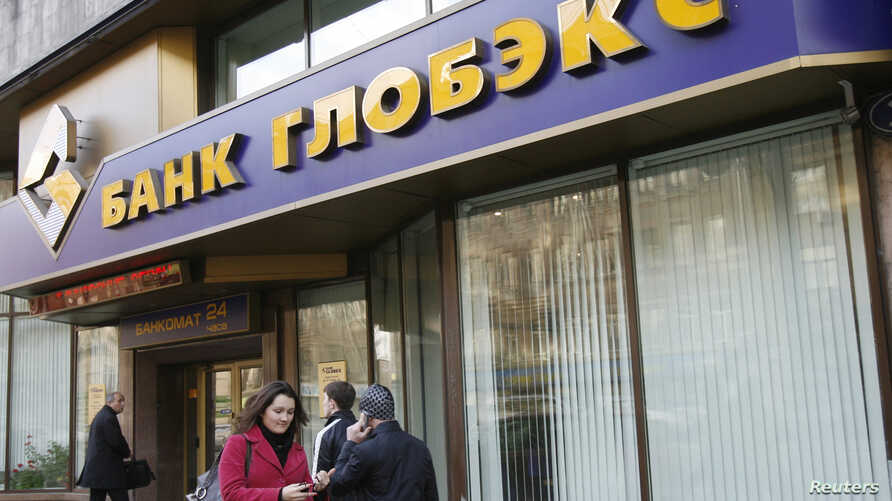 FILE - People walk past a Globex bank office in Moscow, Oct. 16, 2008.