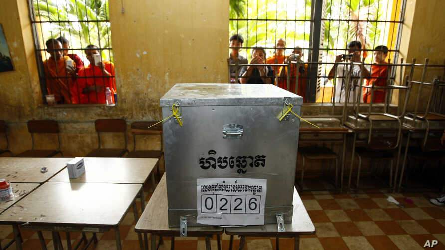 FILE - Young men are seen taking photos of a ballot box at a polling station in Phnom Penh, Cambodia, July 28, 2013.