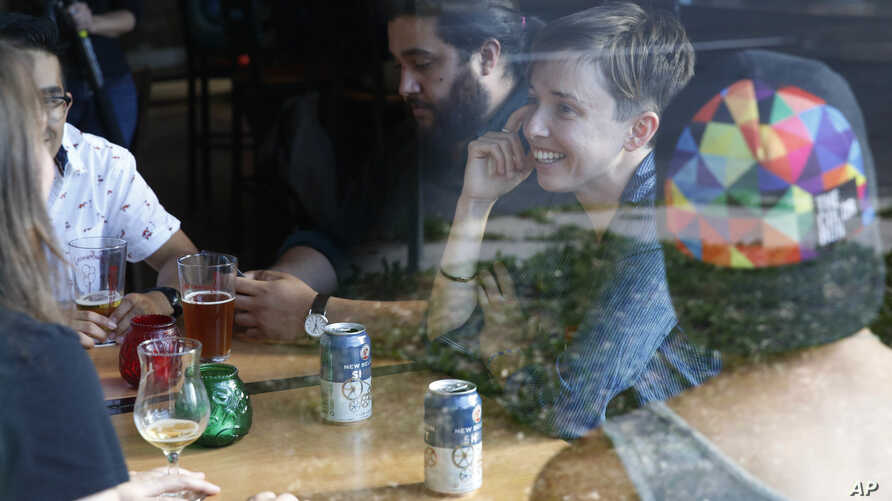Diana Downard, 26, a Bernie Sanders supporter who now says she will vote for Hillary Clinton, has drinks with friends at a pub in Denver, July 6, 2016.