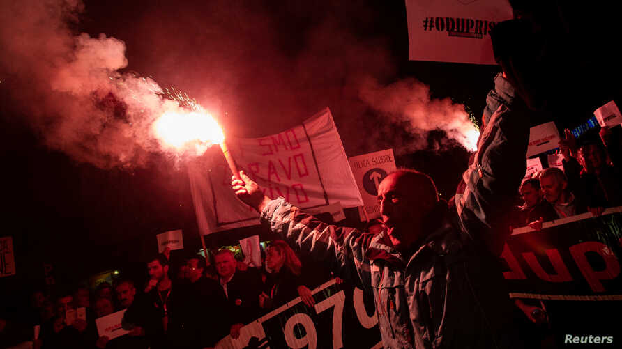 A demonstrator holds a flare during civic protest in Podgorica, Montenegro, March 2, 2019.