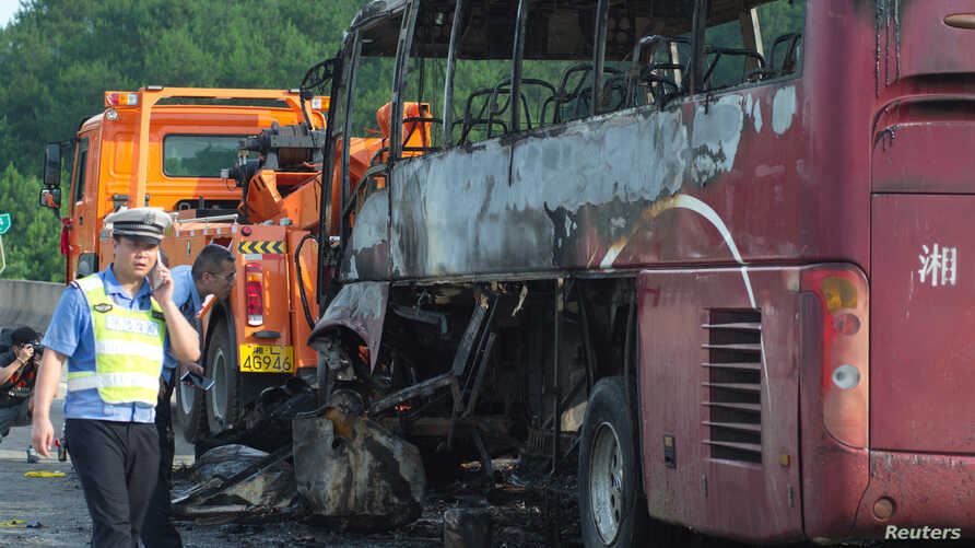 FILE - Police stand next to a burned bus after a fire killed at least 35 people in Yizhang county, Hunan province, China, June 26, 2016. On Friday, a passenger bus and a truck collided, killing 18 and injuring 14 in the province.