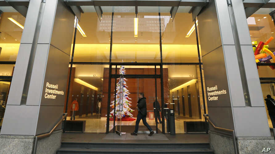 People enter the Russell Investments Center building Monday, Dec. 7, 2015, in Seattle. Over 100 people have gotten sick in a norovirus outbreak at the office building, health officials reported Monday.