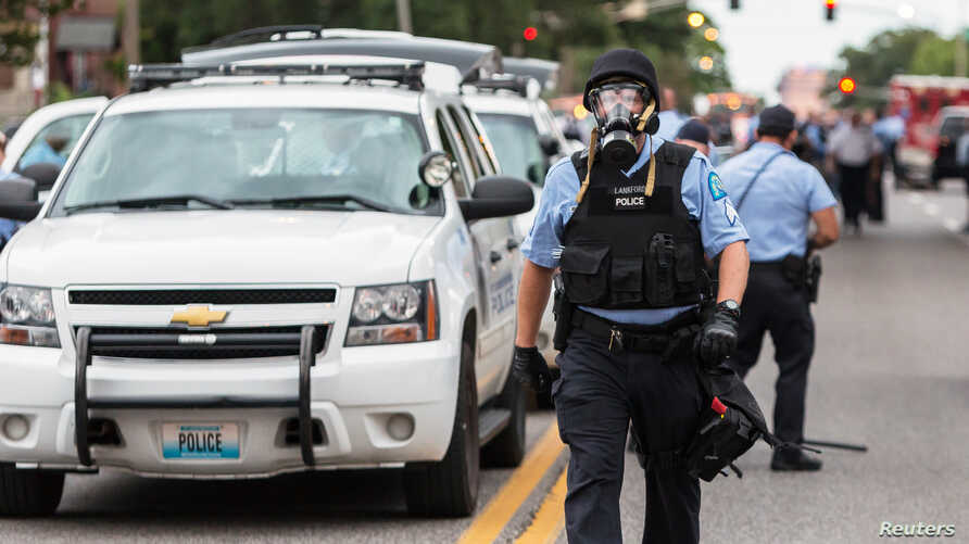 Police wear gas masks as they attempt to disperse a crowd that gathered after a shooting incident in St. Louis, Missouri August 19, 2015. Police fatally shot a black man they say pointed a gun at them, drawing angry crowds and recalling the racial te